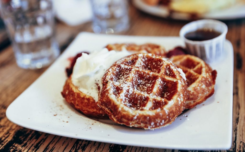 Waffles with whipped cream and syrup cup