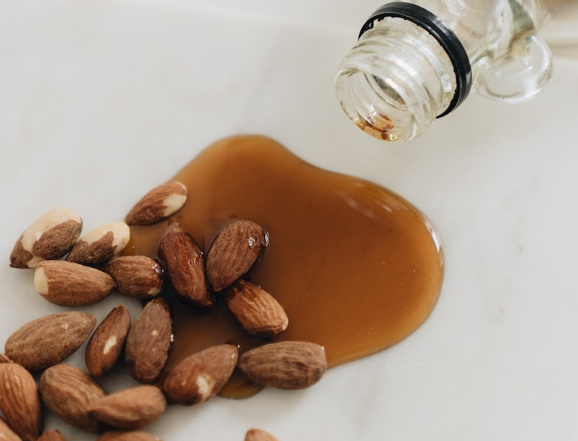 Maple syrup bottle next to almonds with syrup