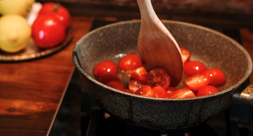Reducing tomatoes in a pan on a burner