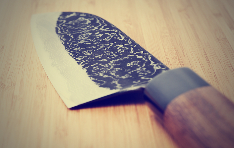 Japanese damascus carbon steel knife on wooden plank, close-up, toned picture