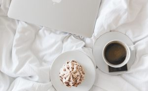 Lpatop with a cream muffin and coffee in bed