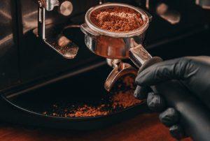 Dry espresso grounds in portafilter over a knock box