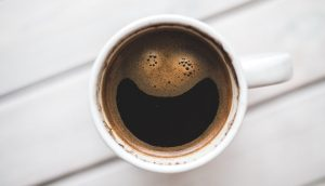 Coffee cup with bubbles making it look like a smile