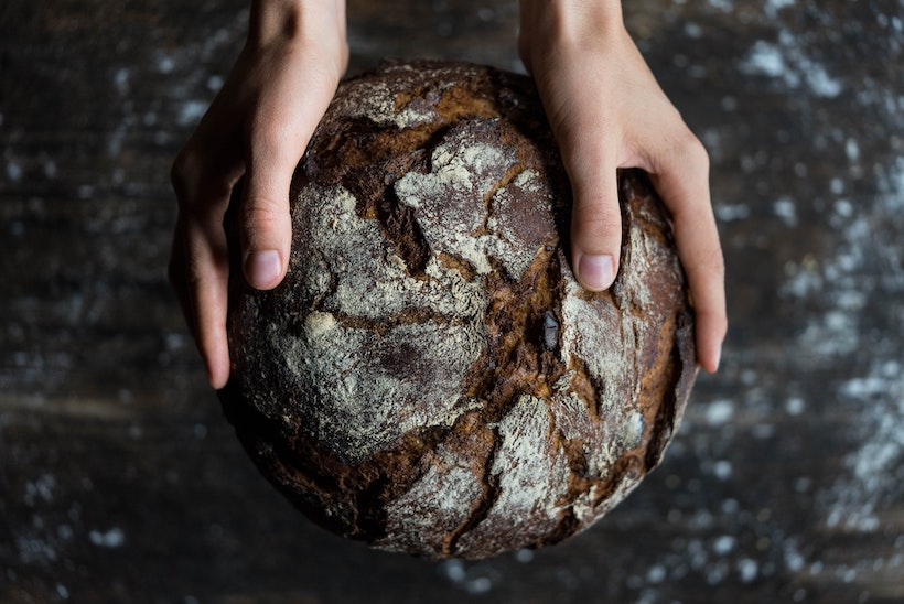 Lady holds round dark bread she baked