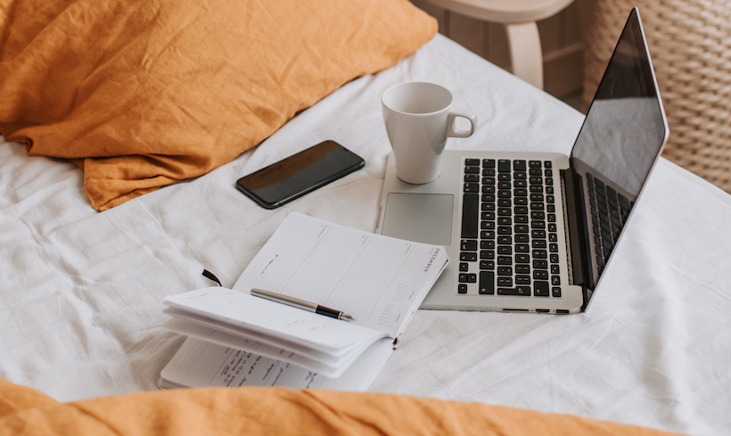 Laptop in bed with coffee and notebook and phone
