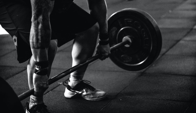 Strong man about to lift a barbell in a deadlift