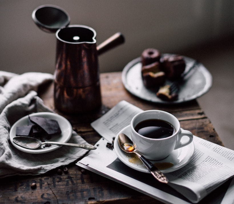 Metal carafe in background of meal with coffee and chocolate