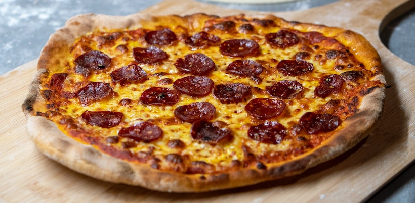 Angled shot of pepperoni pizza on wooden server