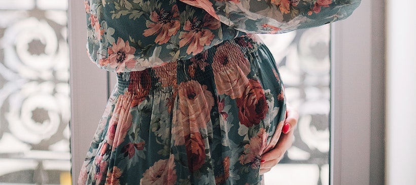 Pregnant lady holding her belly in a dress