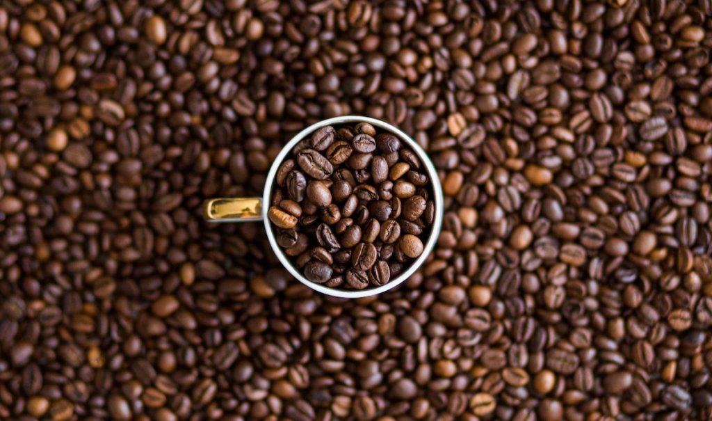 Roasted coffee beans surrounding a white ceramic mug