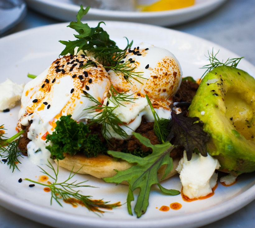 Soft boiled eggs on top of bread with avocado