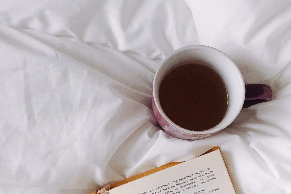 Ceramic mug of herbal tea on white sheets