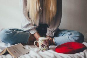 A weoman drinks coffee in bed cross legged