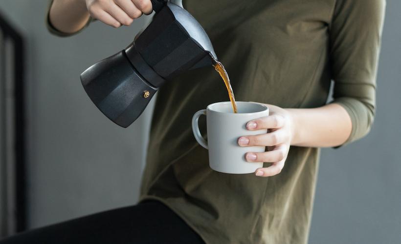 Woman in green shirt pours coffee in mug